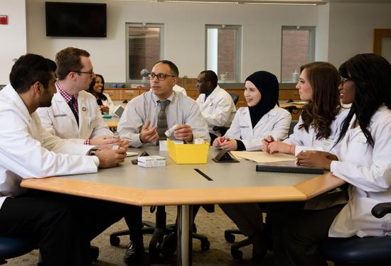 Dr. James Trovato pictured seated a table in the pharmacy practice lab surrounded by five student pharmacists.
