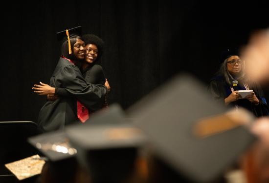 graduate hugs pinner at graduation